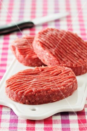 Three raw burgers on a chopping board