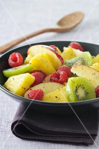 Fruit salad with pineapple, raspberries, apple and kiwi