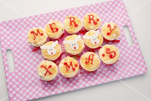 Cupcakes with icing spelling out 'Merry Xmas', on a tray