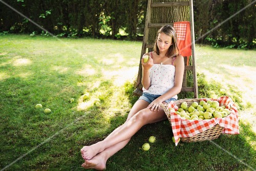 Adolescent girl sitting in orchard eating an apple