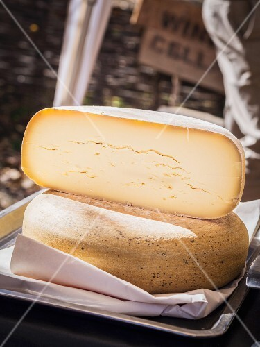 Round Alpkase cheese cut in half.
