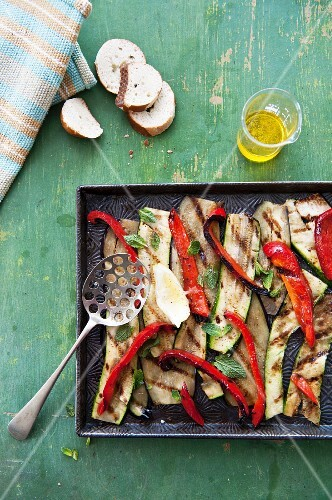 Grilled vegetables on a baking tray, olive oil and slices of white bread