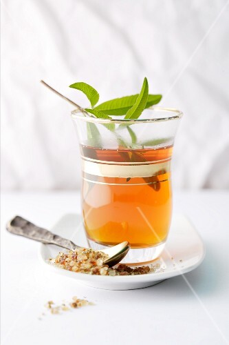 Tea in a glass with a sprig of herbs
