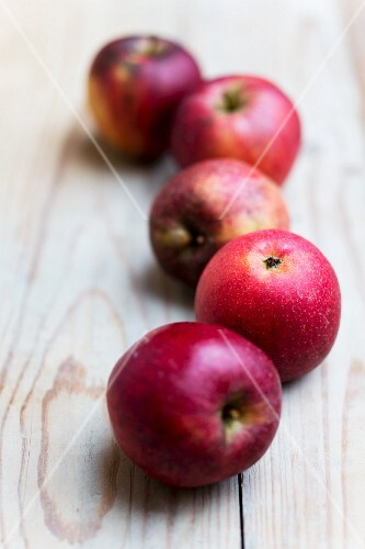 Five red organic apples on a wooden surfac