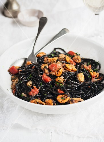 Squid ink spaghetti with mussels and tomatoes