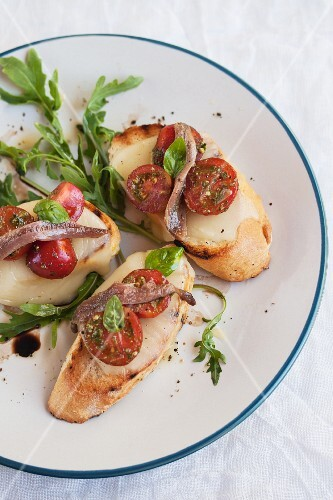 Toasted slices of baguette topped with mozzarella, tomatoes and anchovies