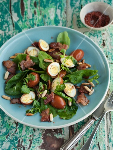 Spinach salad with quail's eggs poached in tea, and bacon