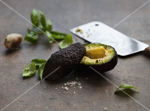 A halved avocado with fresh basil