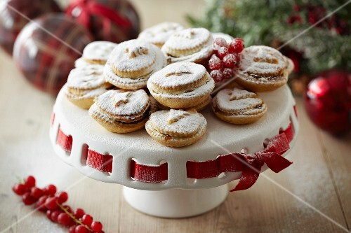 Mince pies with icing sugar on a cake stand for Christmas