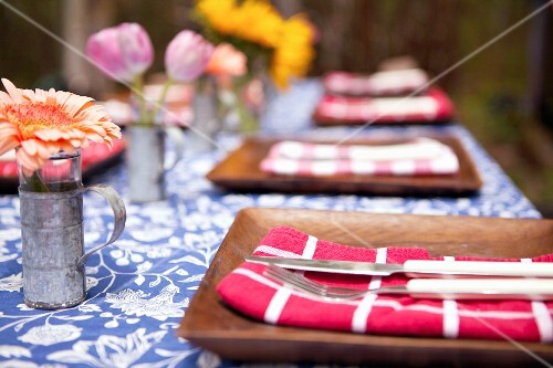 A table laid for a meal outdoors, with brown plates and flowers