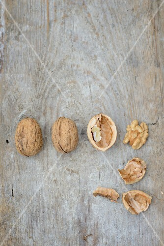 Walnuts, whole and cracked, on a wooden surface