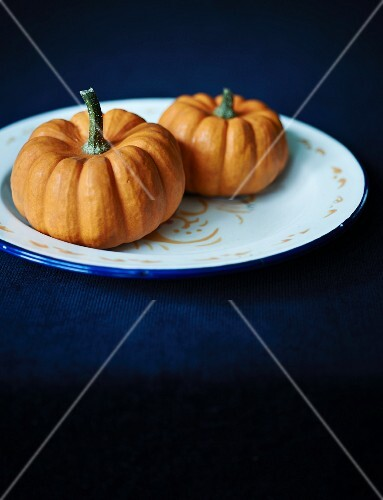 Two orange squashes on a plate