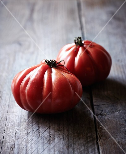 Two beef tomatoes on a wooden surface