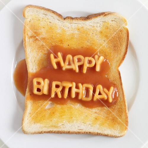 Toast topped with spaghetti letters spelling out HAPPY BIRTHDAY