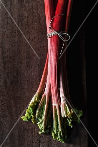 Rhubarb stalks, tied in a bundle, on a wooden surface