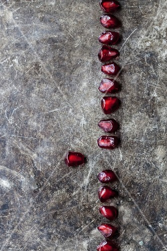 A line of pomegranate seeds on a wooden surface