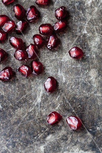 Pomegranate seeds on a stone surface