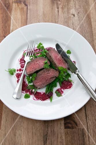 Sliced saddle of venison on green bean salad with beetroot vinaigrette