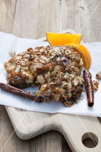 Venison steak with a nut crust, cinnamon and orange wedges