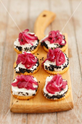 Crackers with goat's cheese, caramelised red onions and black sesame seeds