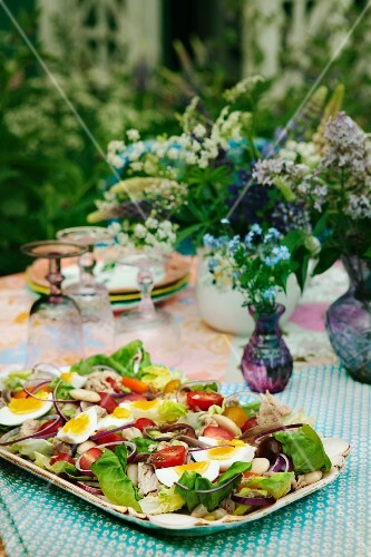 Summer salad with tomatoes and hard-boiled eggs on a garden table (Sweden)