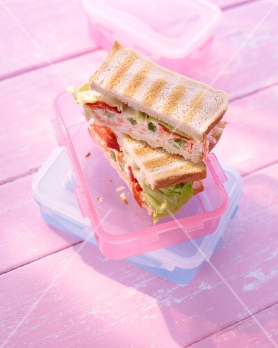 Cream cheese sandwiches in a Tupperware container