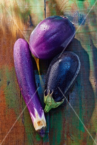 Three assorted aubergines on a wooden surface