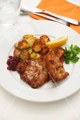 Wiener Schnitzel (breaded veal escalope from Vienna) with roast potatoes, cranberries and lemon