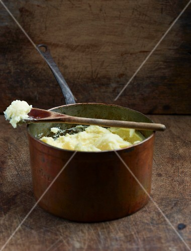 Mashed potato in an old saucepan with a wooden spoon