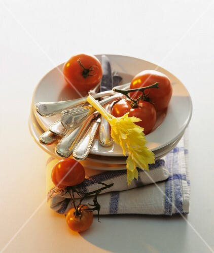 A stack of plates with cutlery and tomatoes