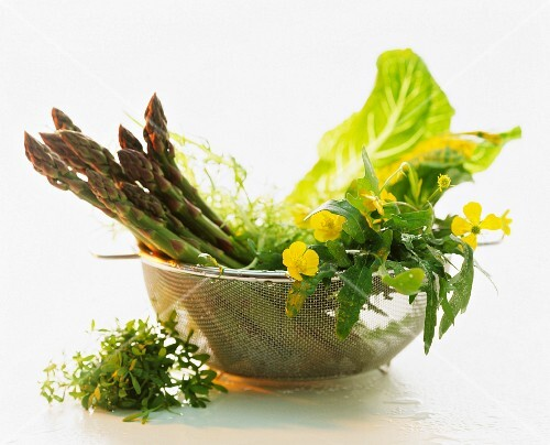 Green asparagus and assorted salad leaves in a colander