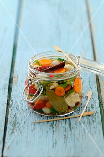 A jar of pickled vegetables with cinnamon and bay leaves