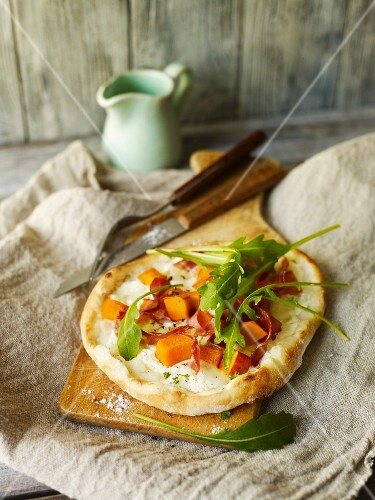 Mini pizza with squash, bacon and rocket