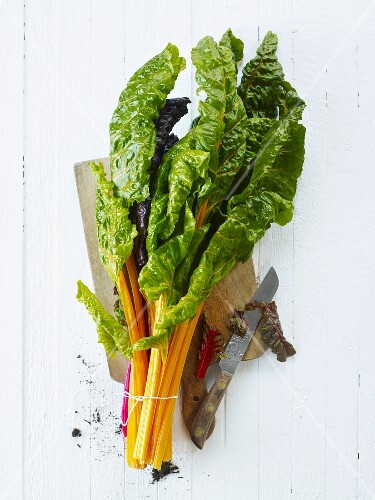 Fresh chard, tied in a bunch, on a chopping board