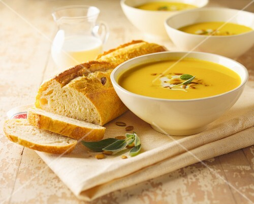 Squash Soup with Sage and Pumpkin Seeds; Sliced Loaf of Bread