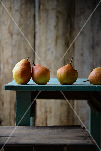 Four pears on a wooden table