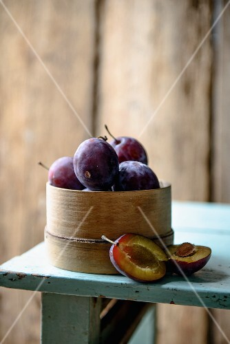 Plums in a woodchip basket on a wooden table