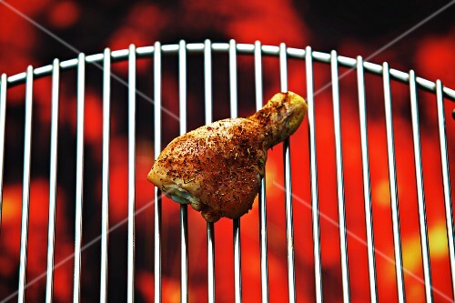 A chicken drumstick on a barbecue