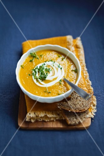 Carrot soup with sour cream, cress and bread