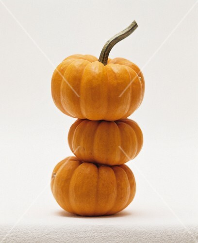 Three orange squash stacked one on top of the other