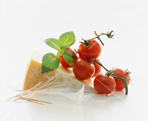 A still life featuring cheese, tomatoes and basil