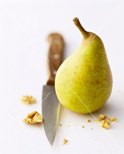A pear with a knife and pieces of walnut