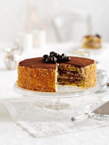 Tiramisu layer cake, partly sliced, on a cake stand