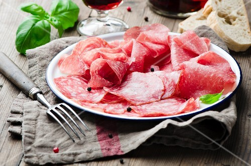 Thinly sliced salami, white bread and red wine