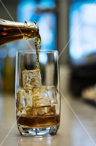 A cola drink being poured into a glass with ice cubes