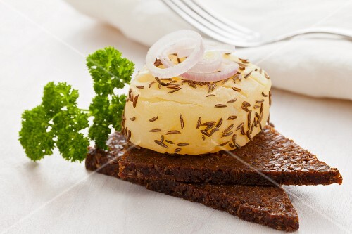 A roll of handmade Harzer (sour milk cheese) with caraway seeds and onions on pumpernickel bread