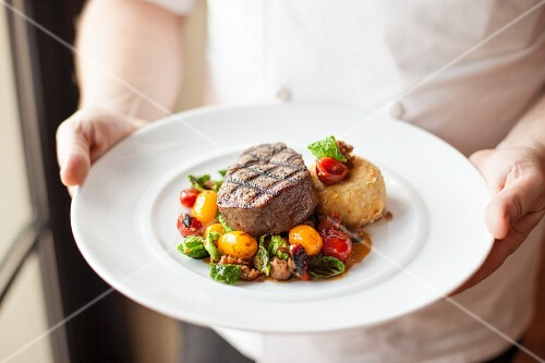Man serving Plate with Beef Filet and Sauteed Vegetable