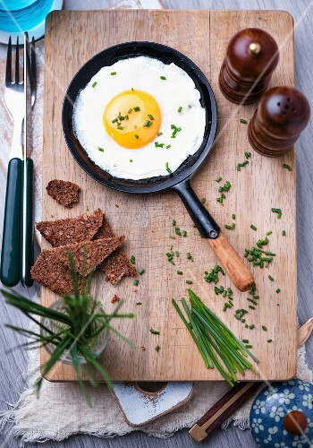 A fried egg with chives in a frying pan, wholegrain bread, salt and black pepper