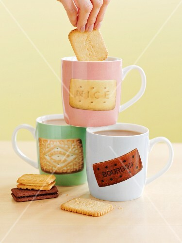 A hand dunking a cookie in a tea mug