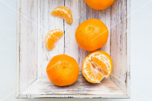 Clementine oranges, whole and peeled, on a wooden tray